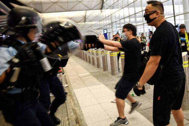 Police scuffle with pro-democracy protestors at Hong Kong's International Airport late on Aug. 13,