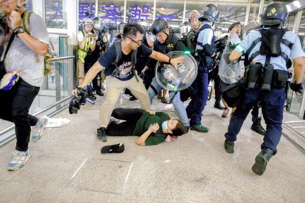 香港国際空港で13日、警官隊と衝突するデモ隊のメンバー=ロイター
