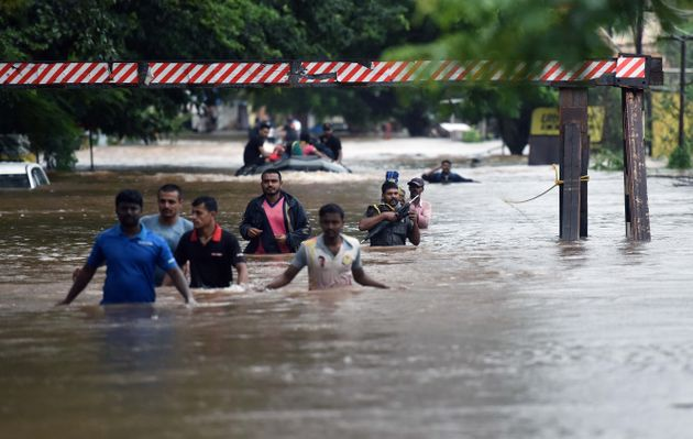 People walk through flooded streets of Sangli on 9 August 2019 in