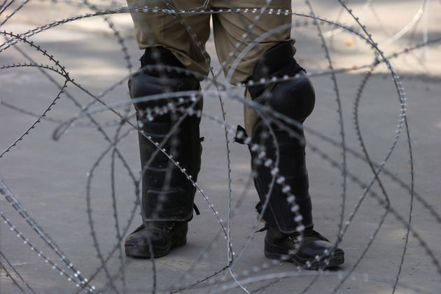 An Indian police officer stands behind the concertina wire during restrictions on Eid-al-Adha after the...