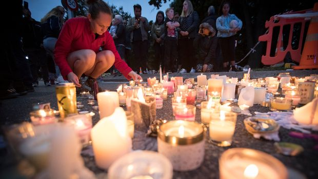 Candles are placed to commemorate victims of Friday's shooting, outside the Al Noor mosque in Christchurch, New Zealand, Monday, March 18, 2019. Three days after Friday's attack, New Zealand's deadliest shooting in modern history, relatives were anxiously waiting for word on when they can bury their loved ones. (AP Photo/Vincent Thian)