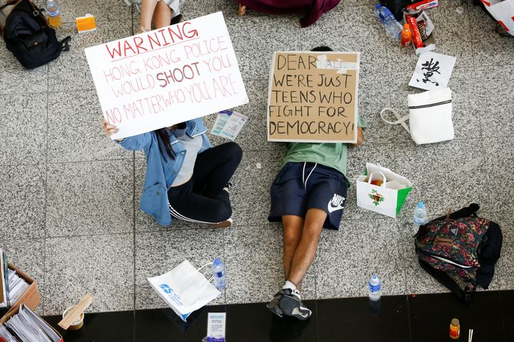 Anti-government demonstrators sit in a designated area of the arrival hall of the airport, after police and protesters clashe