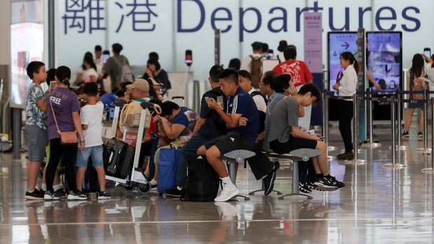 Travelers wait at the airport departure hall in Hong Kong, Wednesday, Aug. 14, 2019. Flights resumed at Hong Kong's airport Wednesday morning after two days of disruptions marked by outbursts of violence highlighting the hardening positions of pro-democracy protesters and the authorities in the Chinese city that's a major international travel hub. (AP Photo/Vincent Thian)