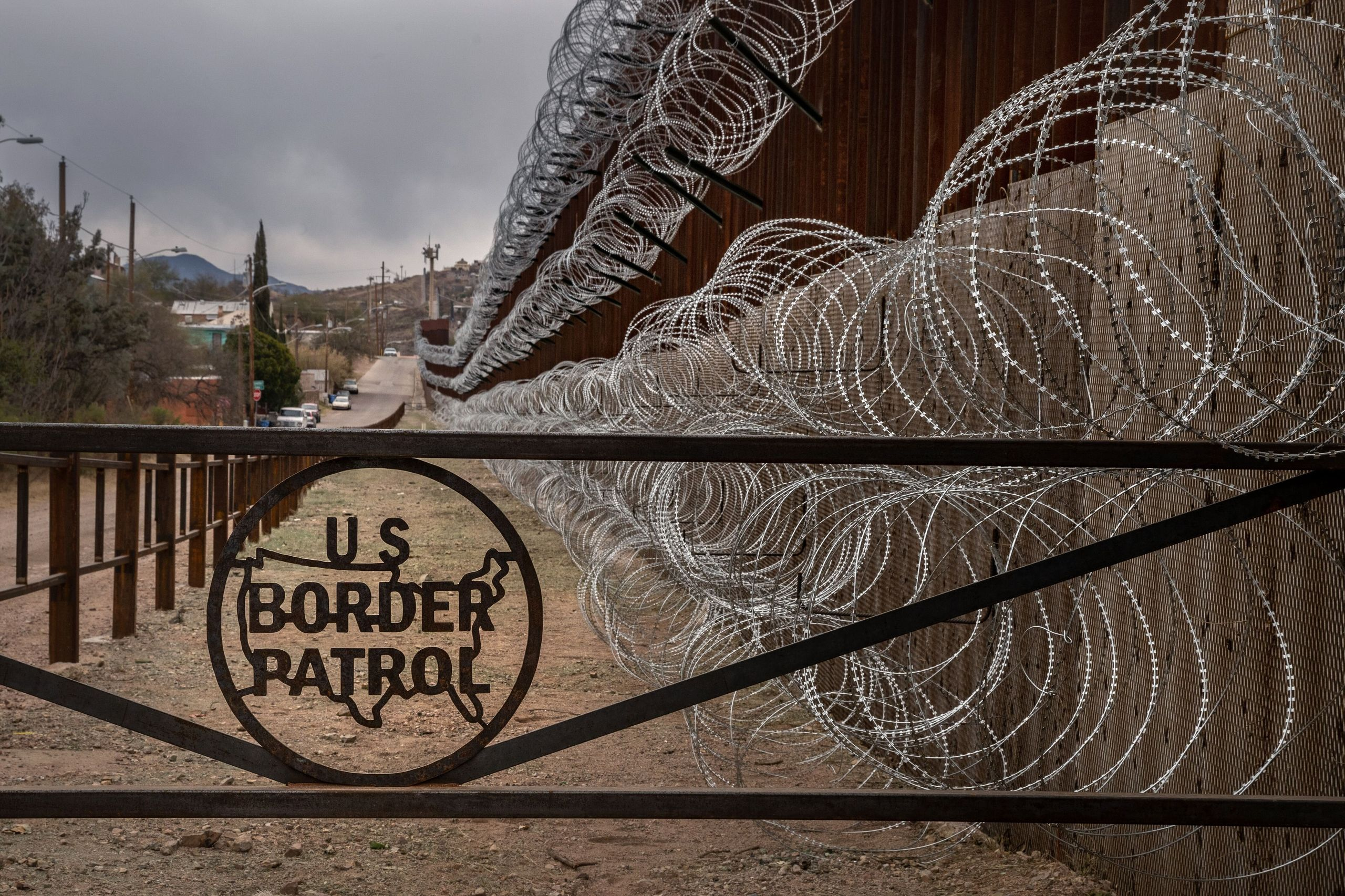 A metal fence marked with the U.S. Border Patrol insignia prevents people from getting close to the barbed/concertina wire co