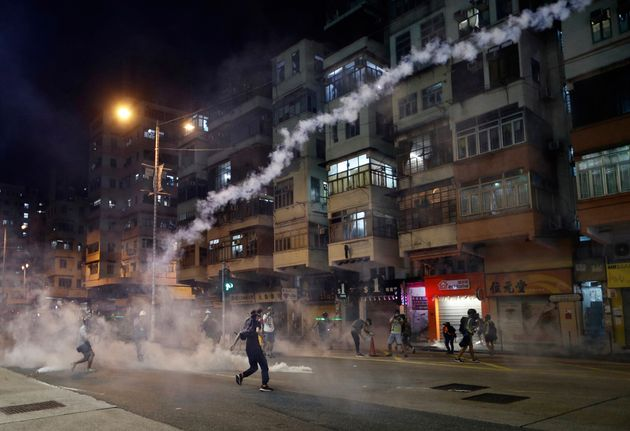 Protesters react to tear gas from Shum Shui Po police station in Hong Kong on Wednesday, Aug. 14,