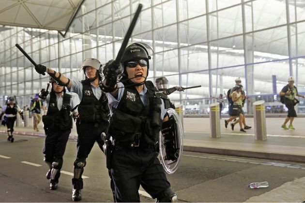 Riot police with batons and shields shout at protesters during a demonstration at the international airport in Hong Kong Aug. 13, 2019.