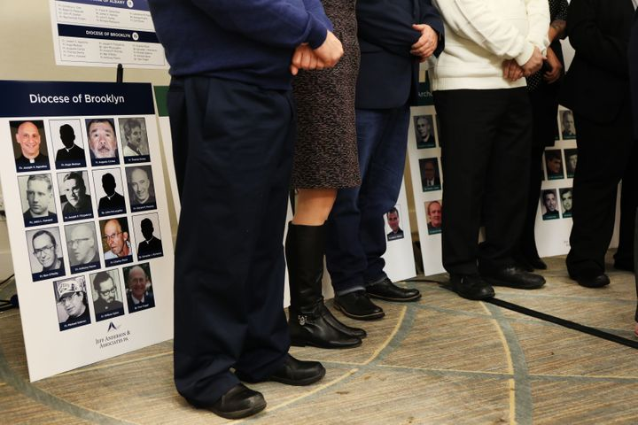 Survivors of sexual abuse by clergy stand before photos of accused men during a news conference with lawyer Jeff Anderson of
