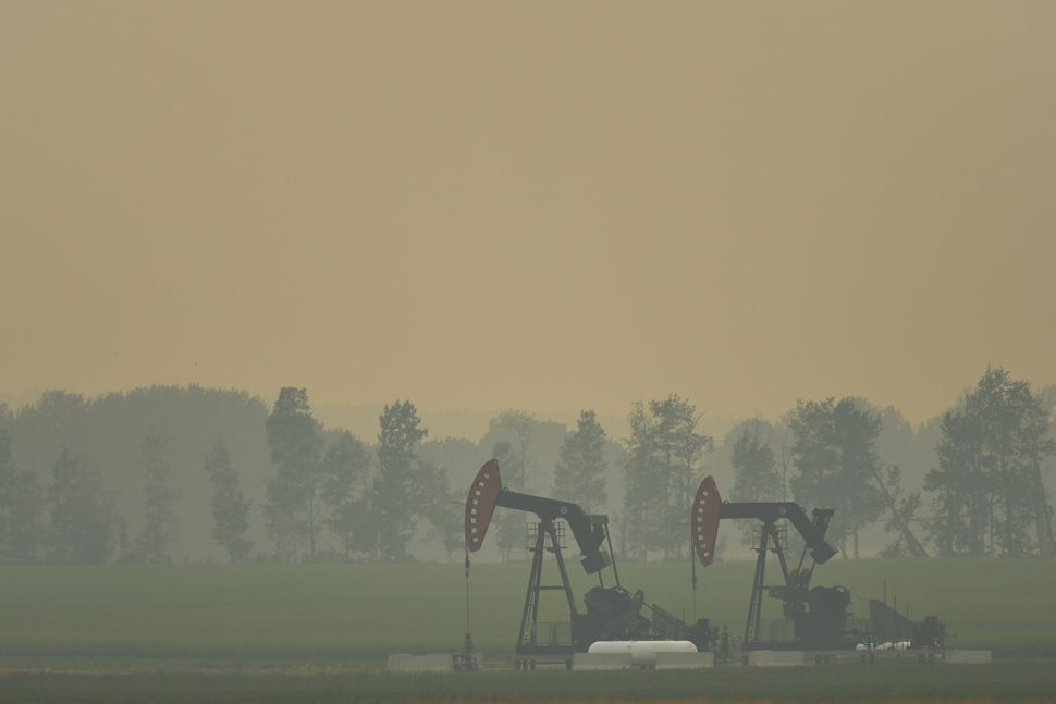 An extraction pump for oil and gas on a field near the town of Sundre during smoky and hazy weather conditions...