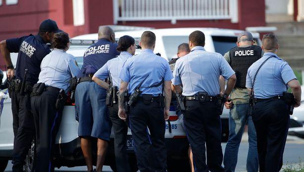 Varios policías de Filadelfia se resguardan detrás de un vehículo durante un tiroteo en el vecindario Nicetown de Filadelfia, el miércoles 14 de agosto de 2019. (AP Foto/Matt Rourke)