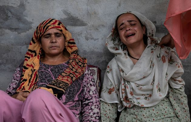 Bilquis, sister of Irfan Ahmad Hurra, cries as their mother Jameela looks on, while they remember Irfan...
