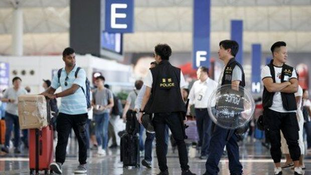 Police patrol the departure hall of the airport in Hong Kong after previous night's clashes with protesters