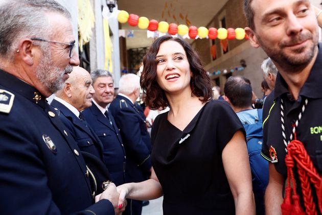 La presidenta de la Comunidad de Madrid, Isabel Díaz Ayuso, saludando a bomberos en las Fiestas...