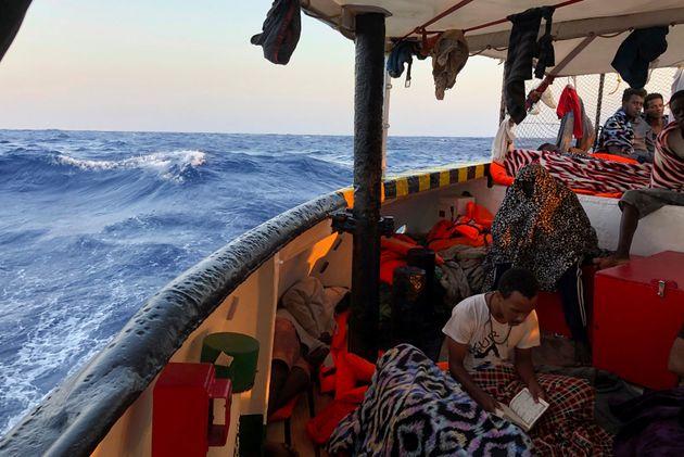 Los migrantes del Open Arms aguardan charlando y leyendo el desembarco en