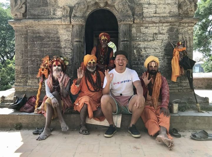 旅行で訪れたネパールの寺院で、地元の人たちと写真を撮る東松寛文さん(右から2人目)