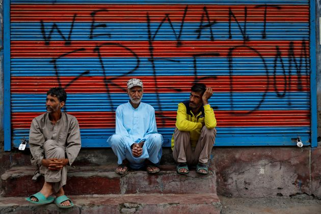 Kashmiri men wait before Eid-al-Adha prayers during restrictions after the scrapping of the special constitutional...