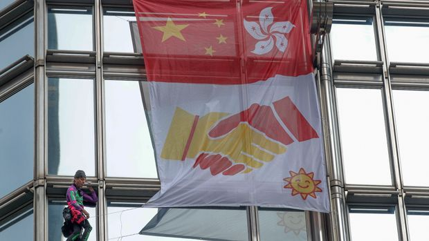 Alain Robert, a French rock and urban climber hangs a large fabric displaying Chinese and Hong Kong flags, shaking hands and shining sun in Cheung kong centre building in Hong Kong, Friday, Aug. 16, 2019. Flights resumed at Hong Kong's airport Wednesday morning after two days of disruptions marked by outbursts of violence that highlight the hardening positions of pro-democracy protesters and the authorities in the semi-autonomous Chinese city. (AP Photo/Vincent Thian)