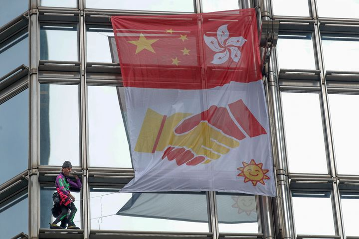 "French ""spiderman"" climber Alain Robert hoisted the flag to encourage reconciliation between China and Hong Kong,"