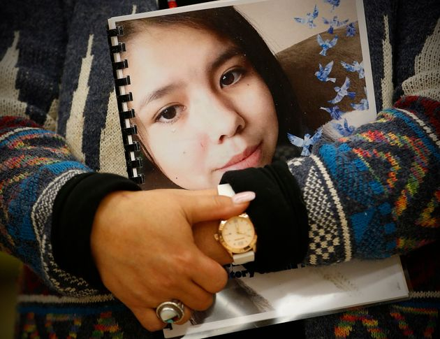 A First Nations woman holds onto a report featuring the face of Tina Fontaine at an event in Manitoba...