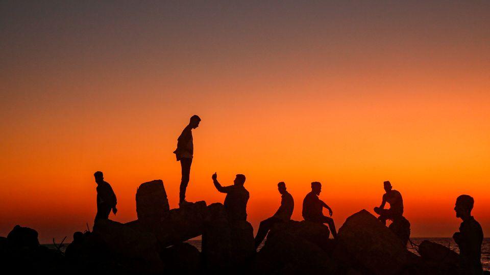 Παλαιστίνιοι, βγάζουν φωτογραφίες καθισμένοι στα βράχια, με φόντο την Μεσόγειο, στην πόλη της Γάζας, στις 13 Αυγούστου, καθώς γιορτάζουν την τρίτη ημέρα του μουσουλμανικού θρησκευτικού φεστιβάλ, του Ιντ αλ - αντχά.