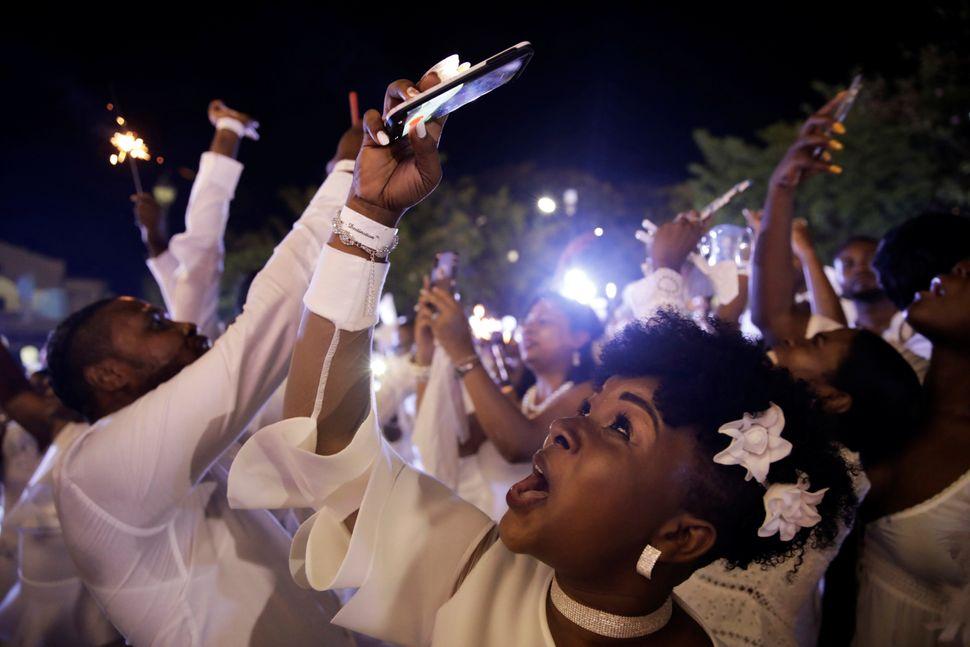 Παρευρισκόμενοι, στην εκδήλωσηHaiti Diner en Blanc, στοCap Haitien της Αϊτής, που πραγματοποιήθηκε στις 10 Αυγούστου, βγάζουν φωτογραφίες από τα βεγγαλικά στον ουρανό.