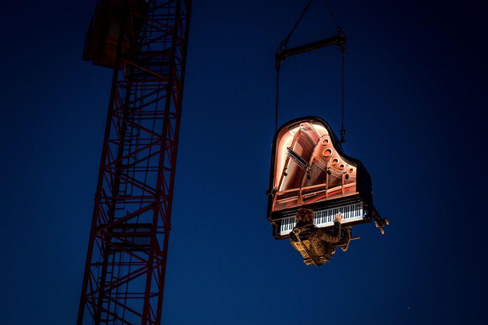 Ο Ελβετός πιανίστας και συνθέτης, Αλαίν Ρος, εκτελεί το «Chantier», ενώ αιωρείται στον αέρα με το μεγάλο του πιάνο, από έναν κινούμενο γερανό, την αυγή στις 16 Αυγούστου 2019, στο 20ο Jeux du Castrum, ένα πολυεπιστημονικό φεστιβάλ στο Yverdon-les-Bains της Ελβετίας .