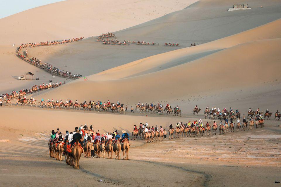 Τουρίστες κάνουν βόλτα με καμήλες, στην έρημο του Ντουνχουάνγκ, στην βορειοδυτική επαρχία Γκανσού της Κίνας, στις 10 Αυγούστου.