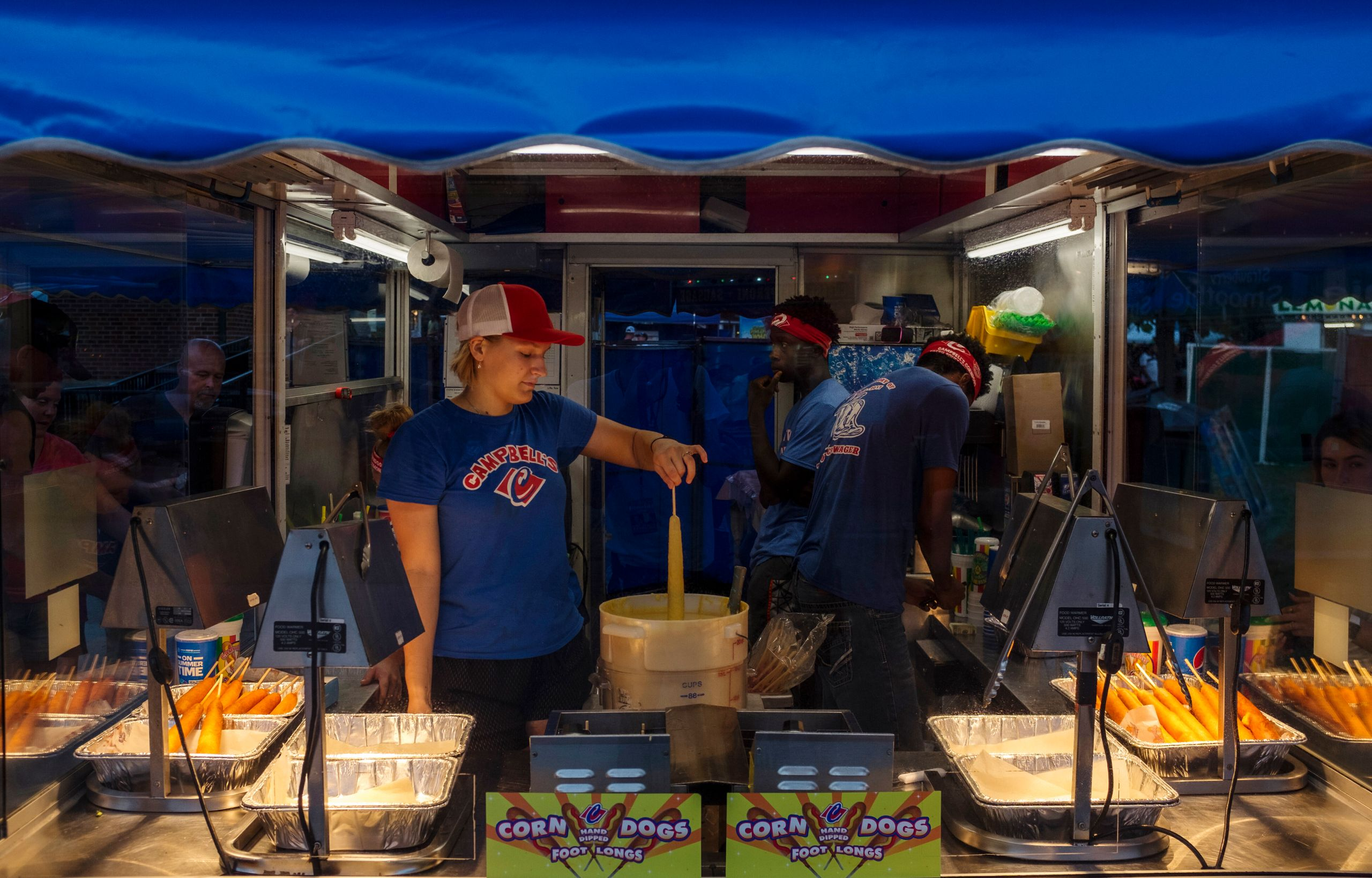 Employees of Campbell's food stand prepare a corndog for the deep-fryer Sunday, Aug. 11, 2019. The Iowa State Fair is k