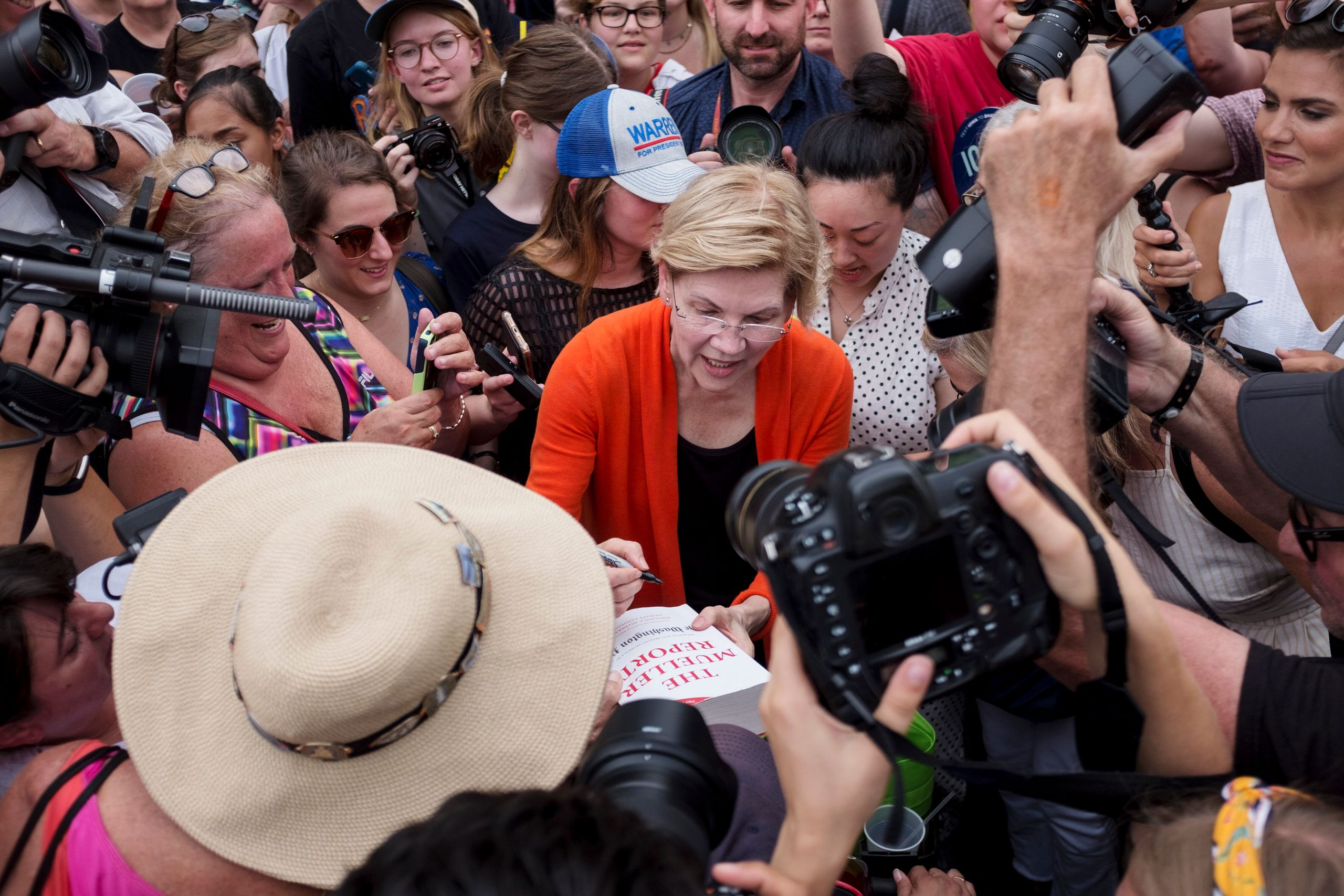 Sen. Elizabeth Warren (D-Mass.) signs a copy of the Mueller report for one of her supporters at the Iowa State Fair on Aug. 1