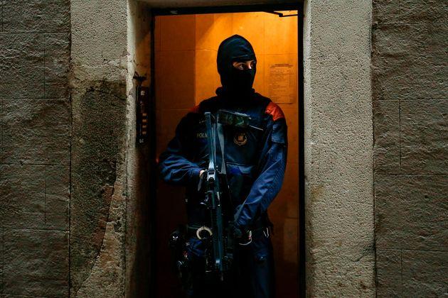 Un mosso d'esquadra armado con un subfusil en una calle de