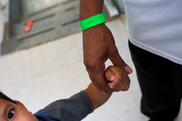 A child grabs the hand of his father at a Catholic shelter in Laredo, Texas, which gives temporary shelter...