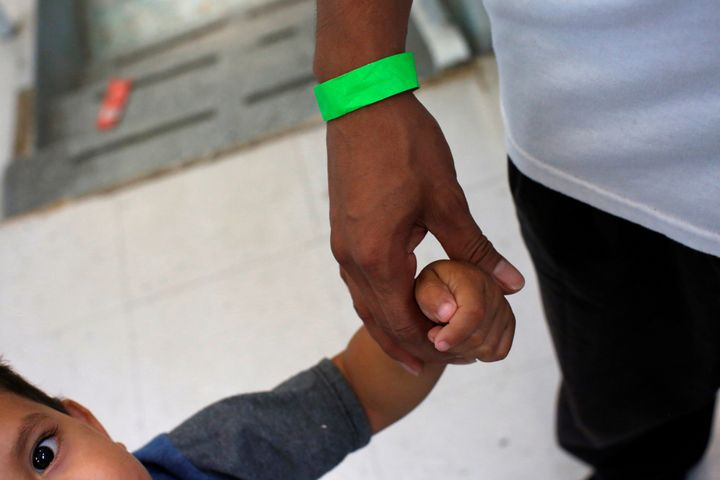 A child grabs the hand of his father at a Catholic shelter in Laredo, Texas, which gives temporary shelter to asylum-seekers from Central American countries released from detention due to overcrowded facilities, on June 4, 2019.