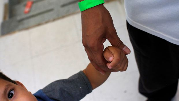 """A Central Americans child grabs the hand of his father at the Catholic shelter """"San Francisco Javier Church"""", which gives temporary shelter to asylum-seekers from Central America countries released by ICE and U.S. Customs and Border Protection (CBP) due to overcrowded facilities ,in Laredo, Texas U.S. June 4, 2019. Picture taken on June 4, 2019. REUTERS/Carlos Jasso"""