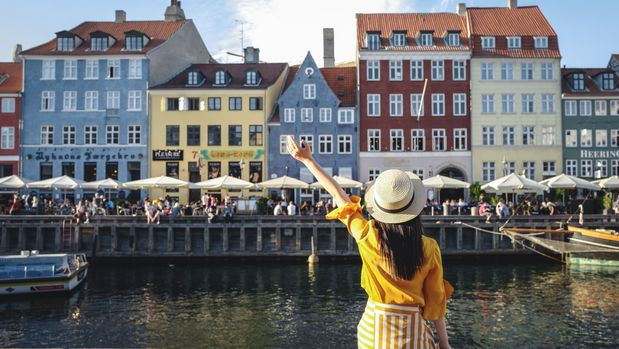 Back view of young woman sitting along famous Nyhavn Canal (New Harbour) after sunset, a 17th-century waterfront canal and entertainment district, landmark of Copenhagen, capital city of Denmark.