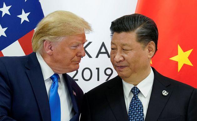 中国の習近平国家主席と握手を交わしながら顔を寄せるアメリカのトランプ大統領=2019年6月29日、G20