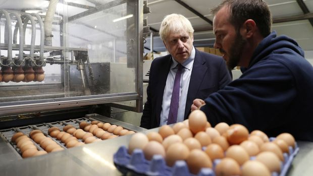 Britain's Prime Minister Boris Johnson inspects the egg operation with local farmer Matt Shervington-Jones, during his visit to rally support for his farming plans post-Brexit, at Shervington Farm, in St Brides Wentlooge near Newport, south Wales, Tuesday,  July 30, 2019. (Adrian Dennis/Pool Photo via AP)