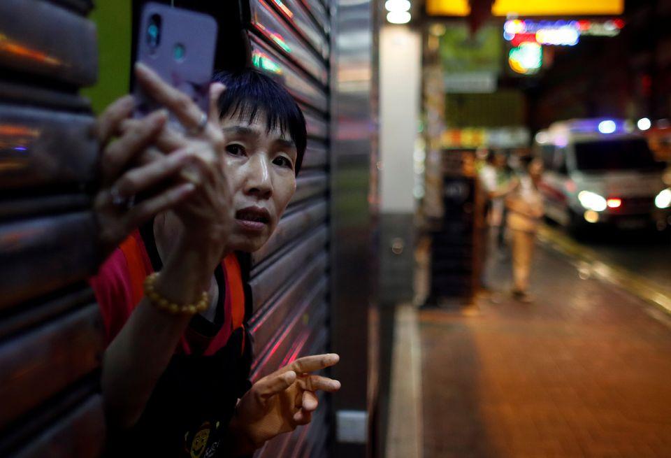 한 주민이 우려스러운 표정으로 바깥을 내다보고 있다. 홍콩. 2019년
