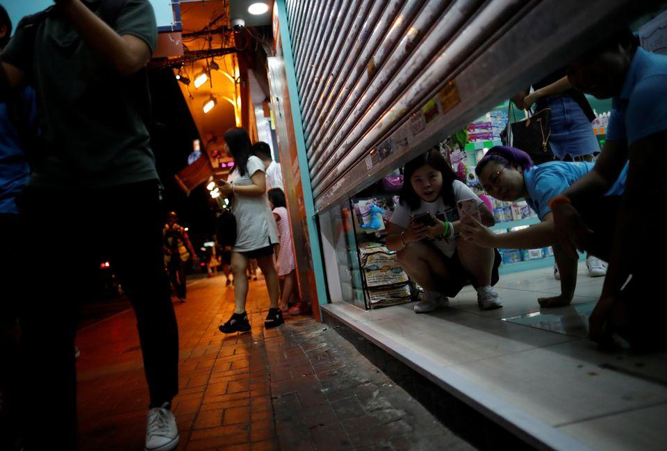 거의 다 내려진 셔터 틈으로 사진을 찍는 주민들의 모습. 홍콩. 2019년