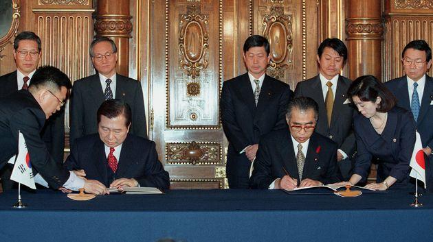 김대중 대통령과 오부치 게이조 일본 총리가 '21세기의 새로운 한일 파트너십 공동선언'에 서명하고 있다. 도쿄, 일본. 1998년