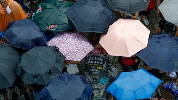 An adult pushes a child on a stroller as protesters brave the rain and gather in Hong Kong Sunday, Aug. 18, 2019. Heavy rain fell on tens of thousands of umbrella-ready protesters Sunday as they started marching from a packed park in central Hong Kong, where mass pro-democracy demonstrations have become a regular weekend activity.  (AP Photo/Vincent Thian)
