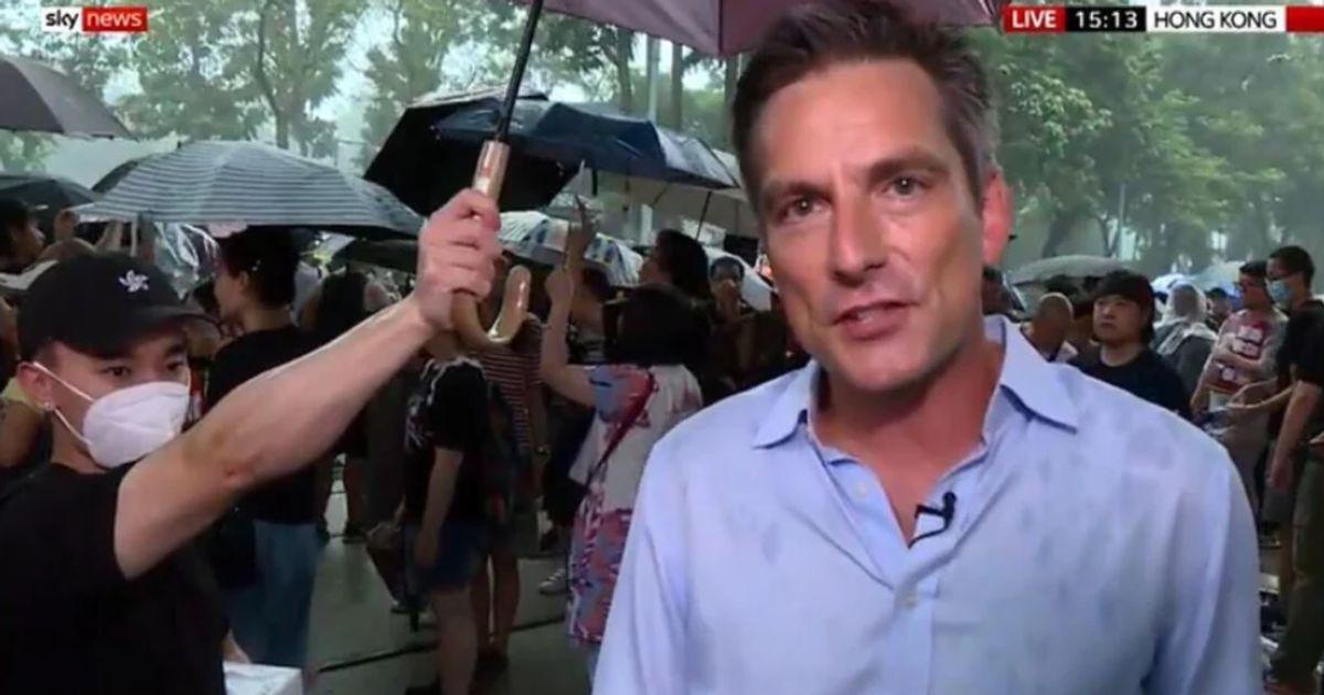À Hong Kong, un manifestant protège un journaliste avec son parapluie