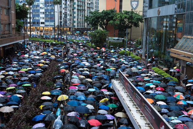 Protesters stand shoulder to shoulder while holding umbrellas during a peaceful