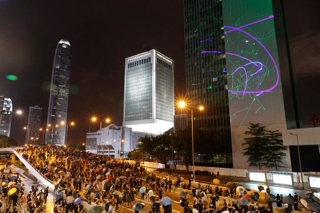 Protesters shine laser pointers on the Government Headquarters complex in Hong Kong, Sunday, Aug. 18,