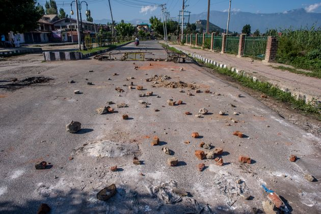 Stones thrown by Kashmiri protesters at security forces lie in the road in the Habba Kadal after...