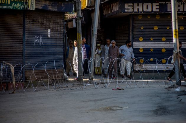 Kashmiris wait to cross through a concertina razor wire cordon as they look towards paramilitary troopers...