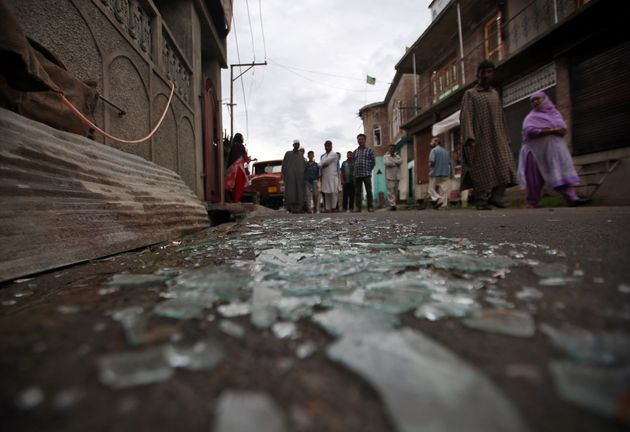 Kashmiris walk past broken window glass after clashes between protesters and the security forces on Friday...