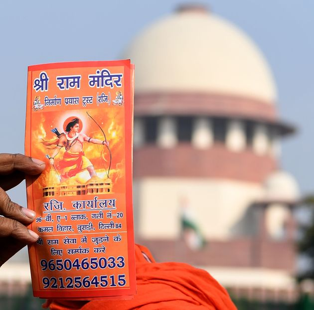 A protester holds a leaflet with the picture of Lord Ram outside the Supreme Court in New Delhi on January...