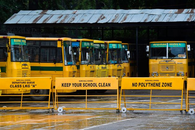 School buses are seen parked in the campus of a closed school in Srinagar on August 19, 2019.