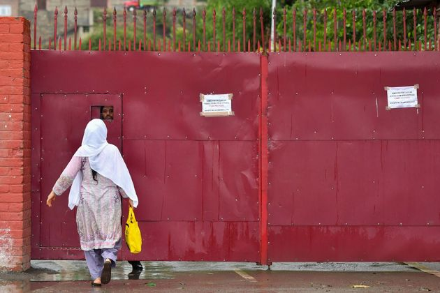 A Kashmiri woman speaks to a worker behind the door of a closed school in Srinagar on August 19,
