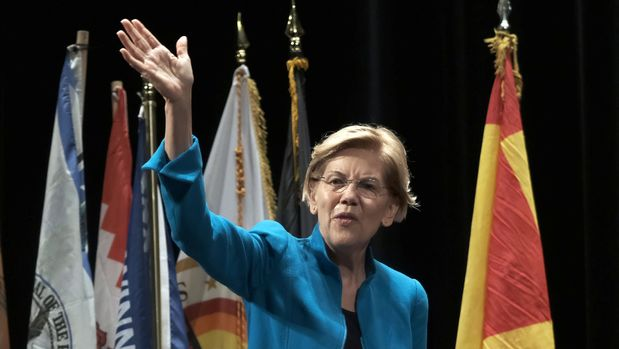 U.S. 2020 Democratic presidential candidate and U.S. Senator Elizabeth Warren waves in front of tribal flags as she speaks at the Frank LaMere Native American Forum while campaigning in Sioux City, Iowa, U.S., August 19, 2019. REUTERS/Alex Wroblewski