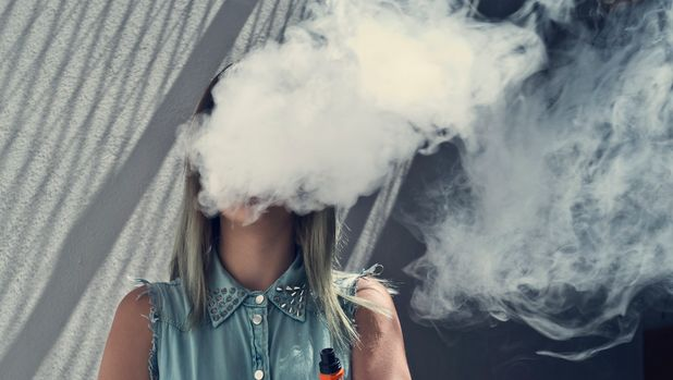 Young woman with her head in a cloud of vapor smoke